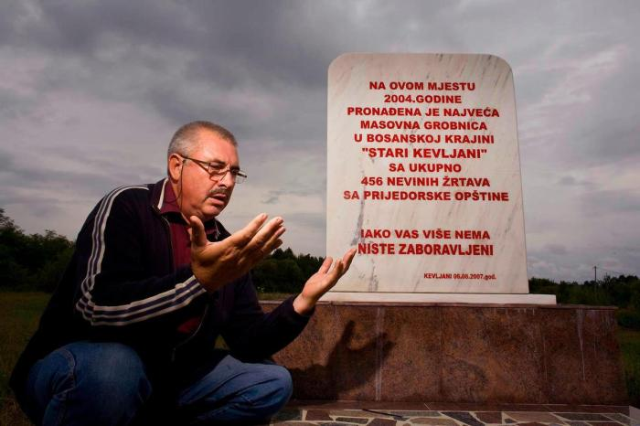 Bosnian Genocide (1992), Bosniak (Bosnian Muslim) man prays above Stari Kevljani mass grave where Serb forces massacred 456 Bosniak women, children and elderly in 1992 (near Prijedor)