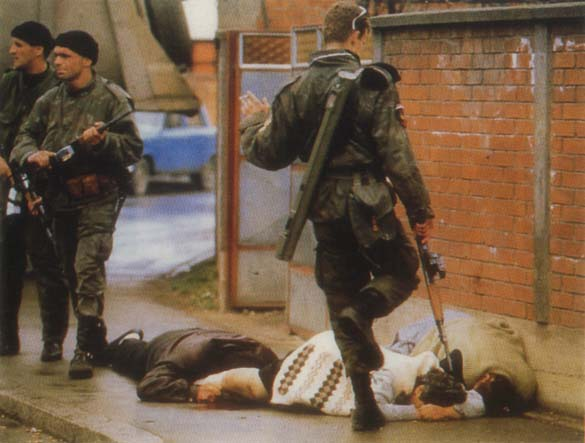 Bosnian Genocide, 1992: Serbian paramilitaries kick and kill Bosniak (Bosnian Muslim) civilians on the streets of Bijeljina on 31 March 1992, the first day of the Bosnian war. Serbian troops slaughtered hundreds of unarmed Bosniak (Bosnian Muslim) civilians - men, women, children and elderly - in during the attack on this norteastern Bosnian city. Photographer: Ron Haviv