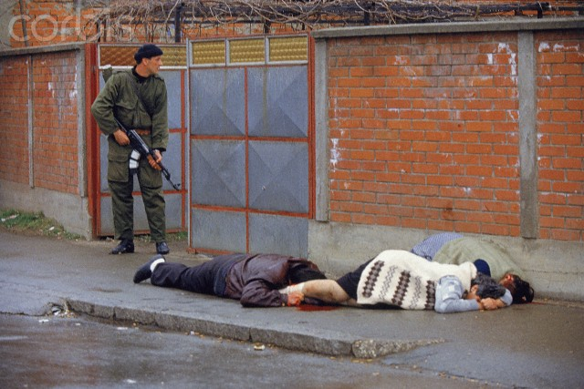 Bosnian Genocide, 1992: A Serbian paramilitary soldier from Arkan's Tigers shoots Bosniak (Bosnian Muslim) civilians in the street of Bijeljina on 31 March 1992, the first day of the Bosnian war.  Photographer: Ron Haviv