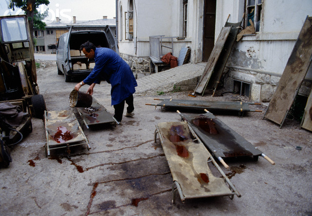 A man in Sarajevo washes blood off of stretchers used to carry the dead and wounded citizens of the besieged capital, terrorized and killed by Serbs on a daily basis.
