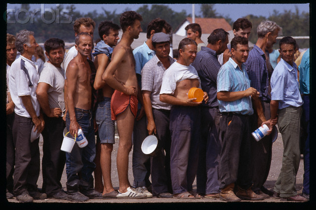 Bosnian Genocide, 1992: Emaciated non-Serb civilians, posing for cameras, line up for food or water during a staged lunch at the Serb-run Trnopolje concentration camp near Prijedor, Bosnia, in August 1992. Thousands of prisoners, mostly Bosniaks (Bosnian Muslims), were tortured and killed there in 1992. Photographer: Antoine Gyori