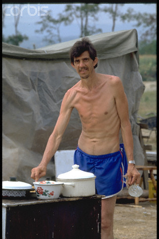 Bosnian Genocide, 1992: Emaciated Bosniak (Bosnian Muslim) man, posing for cameras, during a staged lunch at the Serb-run Trnopolje concentration camp near Prijedor, Bosnia, in August 1992. Thousands of prisoners, mostly Bosniaks (Bosnian Muslims), were tortured and killed there in 1992. Photographer: Patrick Robert