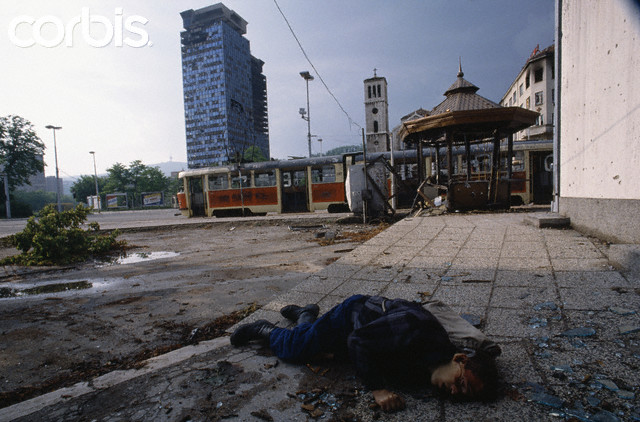 Bosnian Genocide, The body of a civilian victim killed by Serb snipers during the siege of Sarajevo. Dead civilian lies on a sidewalk, surrounded by broken glass.